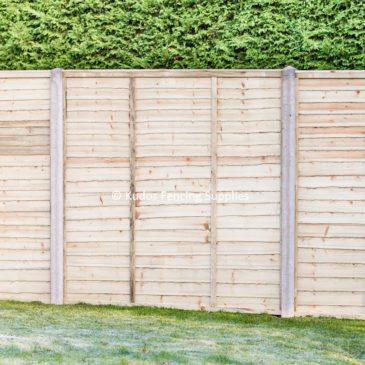 Waney edge lap panels with concrete posts.